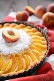 Torta fresca do pêssego polvilhada com o açúcar no fundo de madeira Imagens de Stock