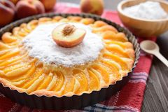 Torta fresca do pêssego polvilhada com o açúcar no fundo de madeira Imagem de Stock Royalty Free