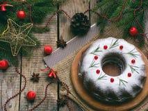 Torta hecha en casa de la Navidad con el arándano y marco de las decoraciones del árbol del Año Nuevo en fondo de madera de la ta Foto de archivo libre de regalías