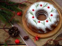 Torta hecha en casa de la Navidad con el arándano y marco de las decoraciones del árbol del Año Nuevo en fondo de madera de la ta Imagen de archivo libre de regalías