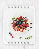 Torta hecha en casa de Pavlova con las bayas frescas del jardín en la bandeja blanca de la hornada sobre fondo de madera ligero Imagen de archivo libre de regalías