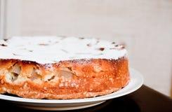 Torta hecha en casa en el plato en la tabla Foto de archivo