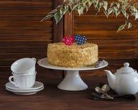 Torta hecha en casa en un soporte de cerámica para la torta, juego de té, corazones de papel, una flor Desayuno romántico del día Foto de archivo