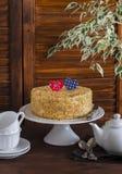 Torta hecha en casa en un soporte de cerámica para la torta, juego de té, corazones de papel, una flor Desayuno romántico del día Fotografía de archivo libre de regalías