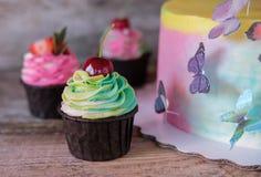 Torta hecha en casa hermosa con las mariposas y las magdalenas Fotos de archivo