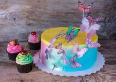 Torta hecha en casa hermosa con las mariposas y las magdalenas Imagenes de archivo