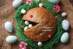 Torta hecha en casa en una jerarquía de la hierba verde falsa y de los huevos de Pascua aislados en textura de la harpillera imagen de archivo libre de regalías