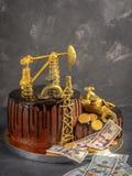 Torta hecha a mano con el esmalte del chocolate, la torre de perforación de aceite y los dólares negros en un fondo concreto gris Fotografía de archivo libre de regalías