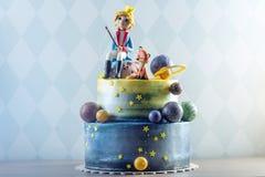 Torta hermosa de los niños grandes adornada bajo la forma de planeta con las estatuillas de la masilla del pequeño príncipe y del Imagen de archivo
