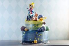 Torta hermosa de los niños grandes adornada bajo la forma de planeta con las estatuillas de la masilla del pequeño príncipe y del Foto de archivo