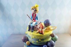 Torta hermosa de los niños grandes adornada bajo la forma de planeta con las estatuillas de la masilla del pequeño príncipe y del Foto de archivo libre de regalías
