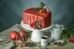 Torta hermosa del terciopelo adornada en el top con el serbal y la granada en una tabla de madera Concepto todavía del otoño de v Fotos de archivo libres de regalías