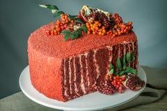 Torta hermosa del terciopelo adornada en el top con el serbal y la granada en una tabla de madera Concepto todavía del otoño de v Imagen de archivo libre de regalías