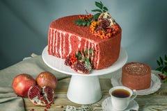 Torta hermosa del terciopelo adornada en el top con el serbal y la granada en una tabla de madera Concepto todavía del otoño de v Foto de archivo