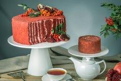 Torta hermosa del terciopelo adornada en el top con el serbal y la granada en una tabla de madera Concepto todavía del otoño de v Fotografía de archivo