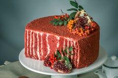 Torta hermosa del terciopelo adornada en el top con el serbal y la granada en una tabla de madera Concepto todavía del otoño de v Fotografía de archivo libre de regalías