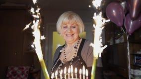 Torta mayor feliz de la tenencia de la mujer Celebrando aniversario del cumpleaños en casa almacen de metraje de vídeo