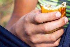 torta Metade-comida em suas mãos foto de stock