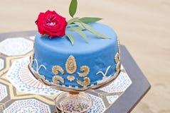 Torta nunziale blu su una tavola e sulle rose rosse sulla cima Immagine Stock