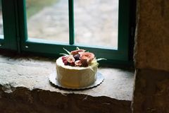 Torta nunziale casalinga decorata con i fiori ed i frutti Immagine Stock