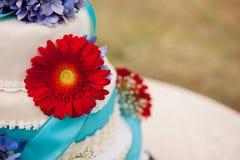 Torta nunziale con un fiore rosso Fotografia Stock Libera da Diritti
