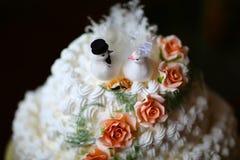 Torta nunziale cremosa bianca con i piccioni e le fedi nuziali decorati con le rose immagini stock libere da diritti