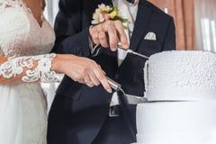 Torta nunziale del taglio delle spose fotografia stock
