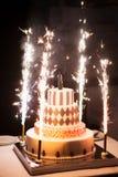 Torta nunziale festiva con i fuochi d'artificio su un fondo scuro Immagine Stock