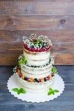 Torta nunziale stratificata tre con le bacche e le foglie del basilico Fotografie Stock