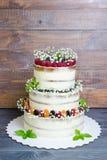 Torta nunziale stratificata tre con le bacche e le foglie del basilico Fotografia Stock
