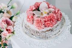 Torta nunziale su un piedistallo bianco decorato con i fiori freschi Immagini Stock Libere da Diritti