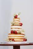 Torta nunziale a tre ripiani con le fragole sulla tavola fotografia stock