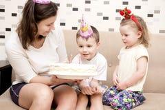 Torta para el cumpleaños del niño La mamá sostiene la torta de cumpleaños para el cumpleaños del ` s de los niños foto de archivo