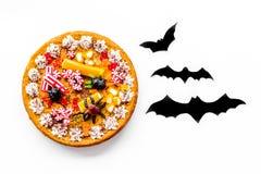 Torta para o Dia das Bruxas com as aranhas gomosas perto dos bastões de papel na opinião superior do fundo branco Imagens de Stock Royalty Free