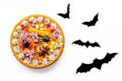 Torta per Halloween con i ragni gommosi vicino ai pipistrelli di carta sulla vista superiore del fondo bianco Immagini Stock Libere da Diritti