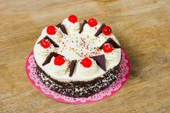 Torta poner crema con la jalea roja en el top Foto de archivo