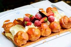 Torta poner crema con las frambuesas y las fresas Imágenes de archivo libres de regalías