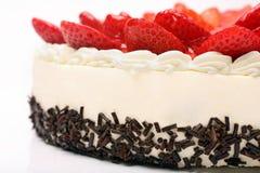 Torta poner crema con las fresas en el fondo blanco Foto de archivo libre de regalías