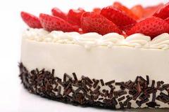 Torta poner crema con las fresas en el fondo blanco Fotos de archivo
