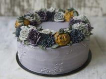 Torta poner crema gris adornada con las flores y las calabazas oscuras del buttercream en fondo rústico Torta de Halloween Torta  imagen de archivo