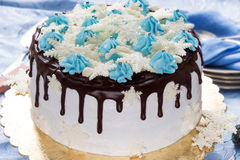 Torta poner crema hermosa adornada con los escapes del chocolate, la crema y los copos de nieve del azúcar de la masilla Imágenes de archivo libres de regalías