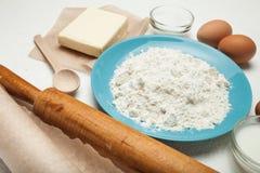 Torta que cuece, receta de la torta, ingredientes - huevos, harina, mantequilla, azúcar en la tabla El concepto de torta dulce imagen de archivo