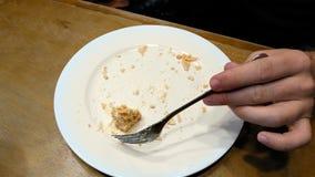Torta que es cortada con la bifurcación en la placa blanca y comida Imagen de archivo
