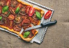 Torta rústica do outono do tomate com manjericão, tomilho e os tomates frescos sobre Fotografia de Stock