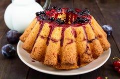 Torta recientemente cocida grande con las bayas del verano en una tabla de madera oscura Imagenes de archivo