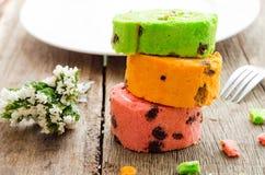 Torta rodada brillante de diverso color en la tabla de madera Foto de archivo