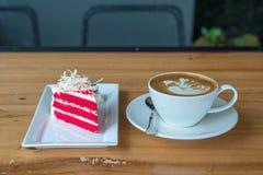 Torta roja del terciopelo en la taza blanca de la placa y de café en la madera Fotos de archivo libres de regalías