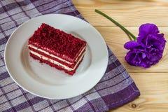 Torta roja del terciopelo y flor púrpura en fondo de madera imagenes de archivo