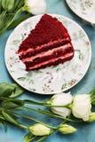 Torta roja en la placa floral con las flores blancas en la tabla azul Imagen de archivo libre de regalías