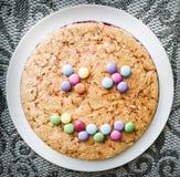 Torta sabrosa con sabelotodos coloridos en la forma divertida de la cara, s festivo imagen de archivo